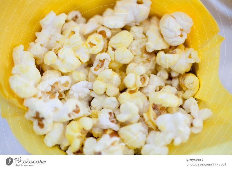 High angle close-up shot of tasty popcorn in yellow paper bag Cinema Paper Delicious Yellow Popcorn food Meal Paper bag Snack Tasty movie hign angle Horizontal
