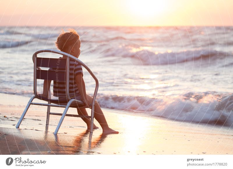 Little boy sitting alone on the chair on the beach and looking at sea waves. Evening sun overshining water Relaxation Vacation & Travel Summer Beach Ocean Chair