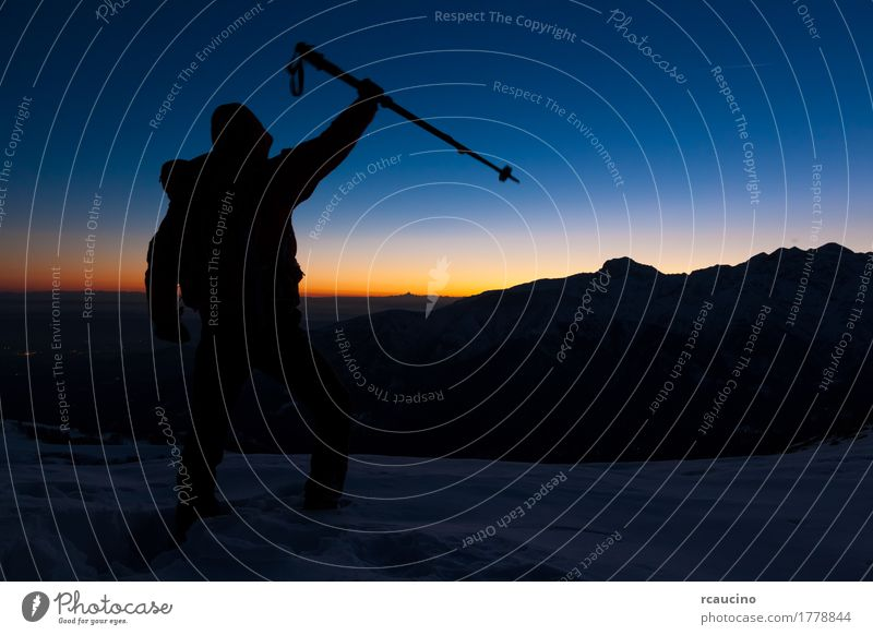 At sunset a man stands on a snowy peak expressing his joy Human being Sky Nature Vacation & Travel Man Blue Beautiful Sun Landscape Loneliness Joy Winter Dark Mountain Adults Sports