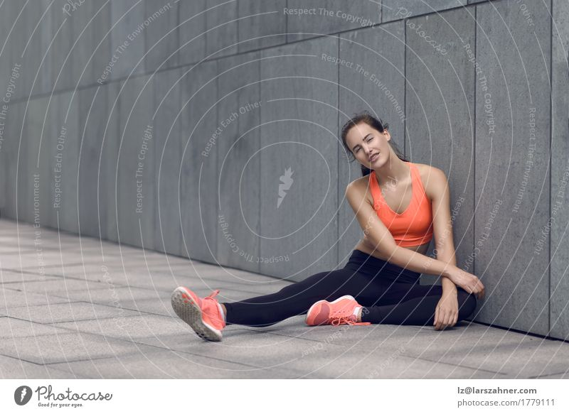 Athletic woman sitting on concrete paving Contentment Feminine Woman Adults 1 Human being 18 - 30 years Youth (Young adults) Tights Brunette Fitness Sit Cute