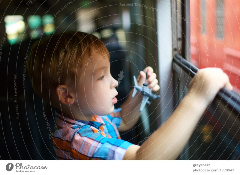 Curious little boy with toy plane looking out of open train window Vacation & Travel Trip Child Human being Boy (child) 1 3 - 8 years Infancy Railroad Blonde