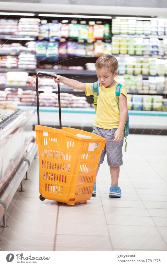 Little boy in the supermarket looking at big full shopping cart. Child going shopping alone Shopping Human being Boy (child) 1 3 - 8 years Infancy
