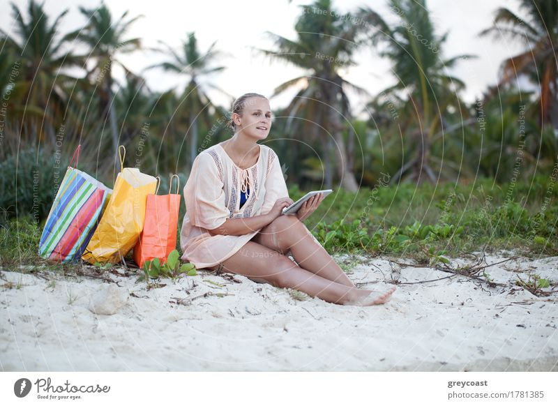 Young smiling woman using tablet computer sitting on the beach after good shopping. Leisure during summer vacation Shopping Exotic Happy Leisure and hobbies