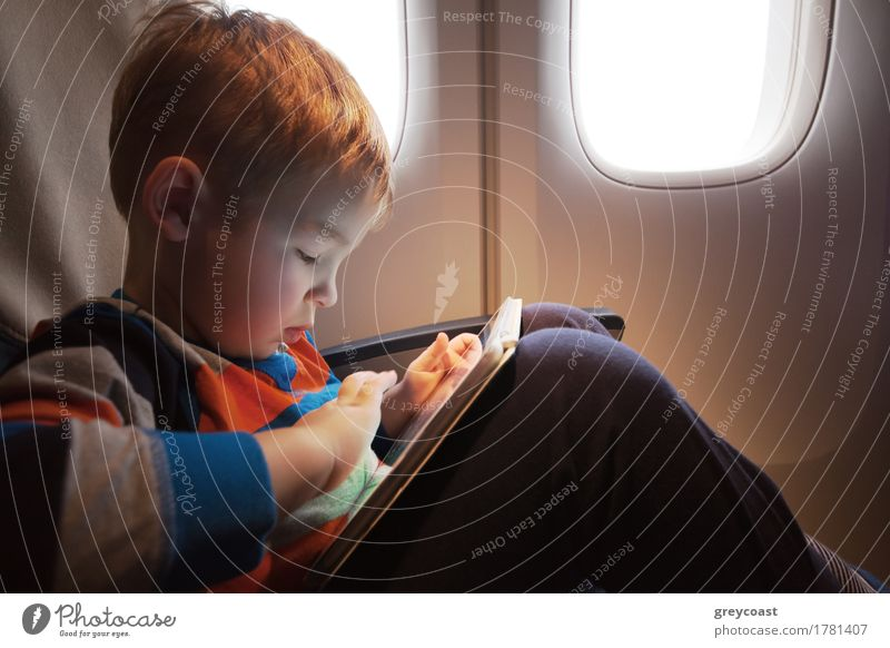 Little child with tablet computer on the lap sitting by the illuminator in the plane Joy Leisure and hobbies Playing Vacation & Travel Trip Entertainment Child