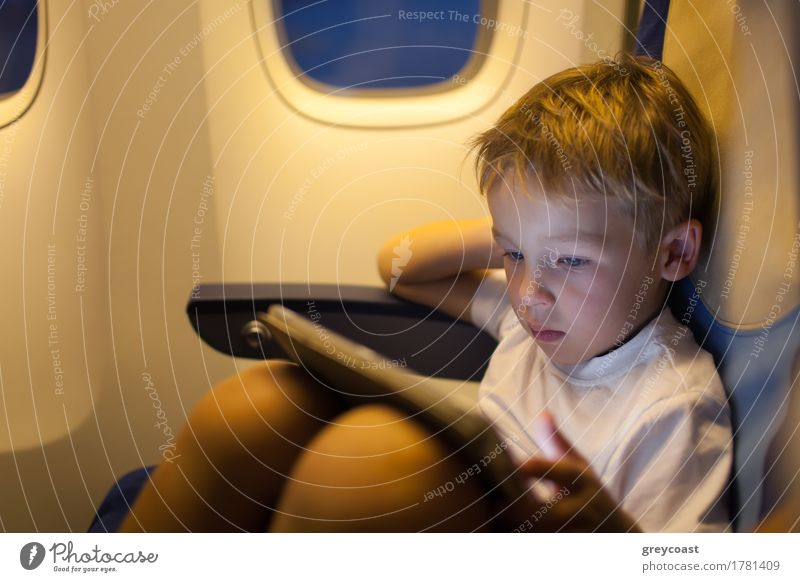 Boy sitting in the plane and using tablet PC Human being Child Vacation & Travel Loneliness Joy Boy (child) Playing Small Leisure and hobbies Trip Modern Action
