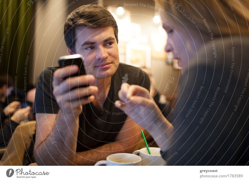 Man using mobile phone during meeting with girl in cafe Human being Youth (Young adults) Young woman Young man Adults Blonde Smiling Telephone Café Meeting Tea