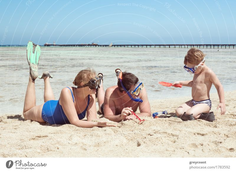 Mother, father and little son on summer vacation at the seaside, They wearing snorkels and flippers while lying and playing on the beach Joy Playing