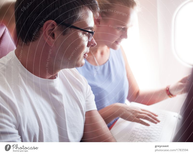 Man and woman are sitting by and watching something in laptop during the flight. Vacation & Travel Trip Business Computer Notebook Technology Young woman