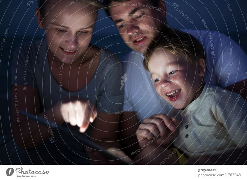 Happy family of three with pad late in the evening. Laughing child looking at screen where mother pointing at something Joy Leisure and hobbies Playing