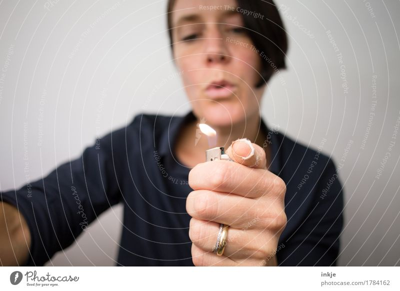 Play with fire Woman Adults Life Face Hand 1 Human being 30 - 45 years Lighter To hold on Simple Hot Threat Safety Senses Ignite Blow Flame Colour photo