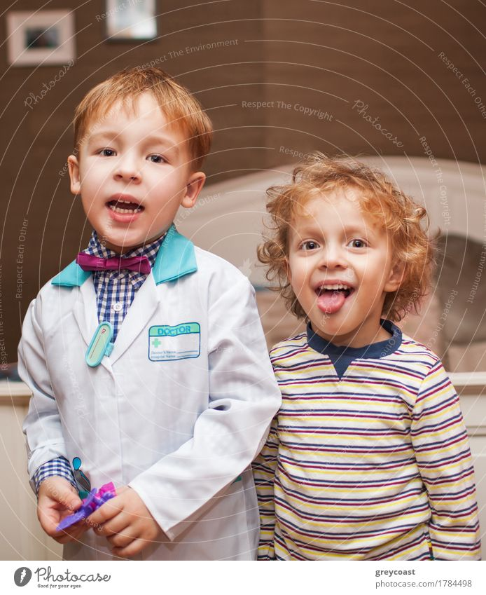 Two little boys as doctor and patient. Doctor is in lab coat, another child showing the tongue while smiling Health care Playing Child Hospital Boy (child)
