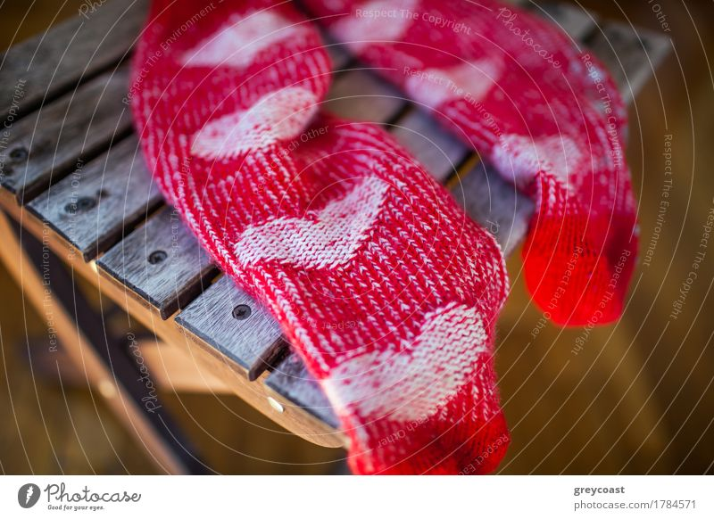 Red socks with heart pattern on wooden chair Furniture Chair Woman Adults Warmth Clothing Footwear Wood Heart Love Bright Cute Brave Romance Knitted Sock pair