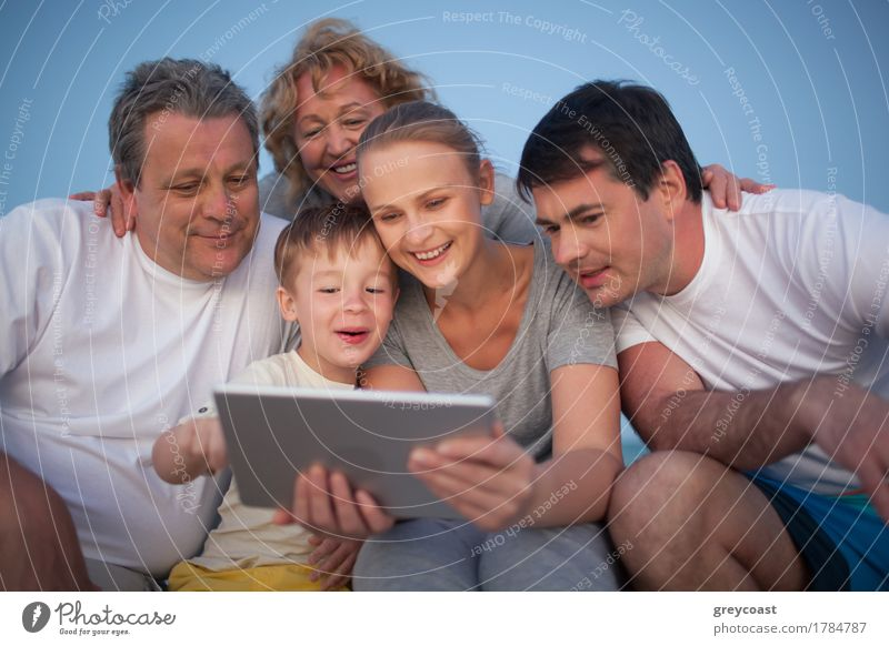 Happy family spending time with pad outdoor Joy Leisure and hobbies Playing Vacation & Travel Summer Beach Ocean Entertainment Child Computer Human being