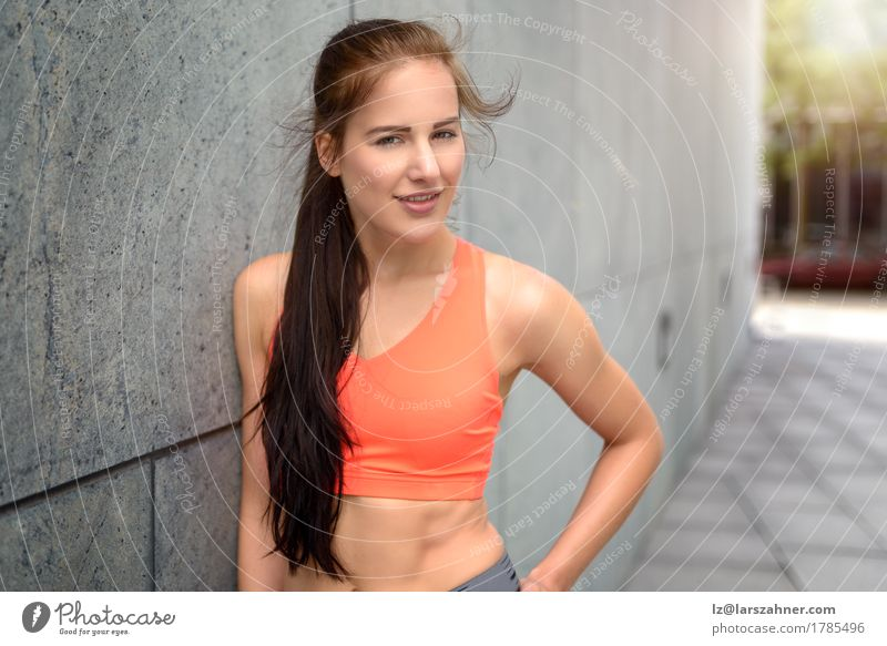 Attractive sporty young woman leaning on a wall Human being Woman Youth (Young adults) Summer 18 - 30 years Face Adults Lifestyle Feminine Happy Copy Space Action Wind Stand Skin Smiling