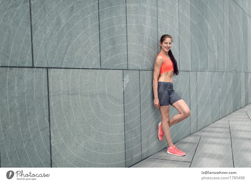 Smiling Trendy Young Woman Standing Against Wall A Royalty
