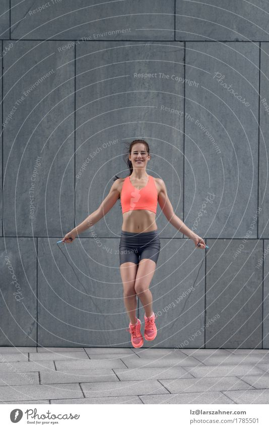 Fit smiling young woman jumping rope Human being Woman Youth (Young adults) 18 - 30 years Adults Lifestyle Happy Jump Copy Space Body Action Fitness Rope Thin Conceptual design Muscular