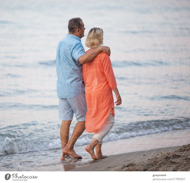 Senior couple walking together along the coast. Man embracing the woman while they having enjoyable barefoot outing on the beach Relaxation Calm