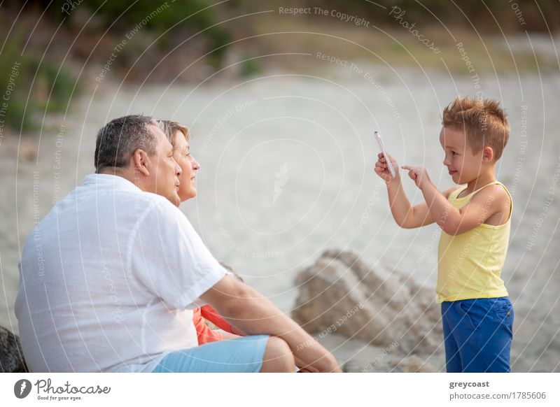 Smiling little child with smart phone taking picture of happy grandmother and grandfather. Family leisure outdoor Happy Summer Beach Child Telephone PDA Camera
