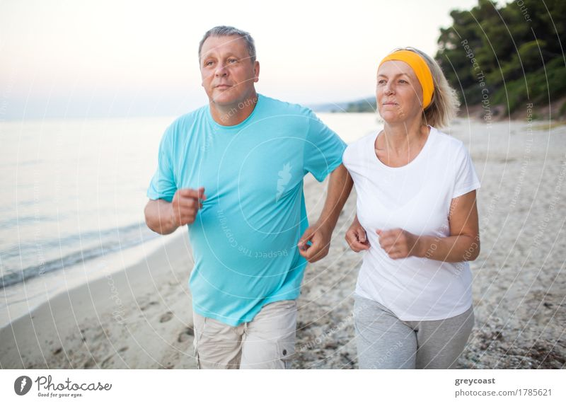 Senior man and woman having a run along the shore. Scene with sea, sand and trees. Healthy and active way of life Lifestyle Leisure and hobbies