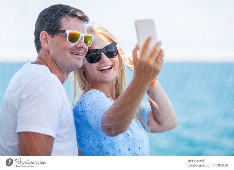 Happy young man and woman in fashionable sunglasses taking cellphone selfie on background of defocused blue sea. Vacation photos Style Vacation & Travel Summer