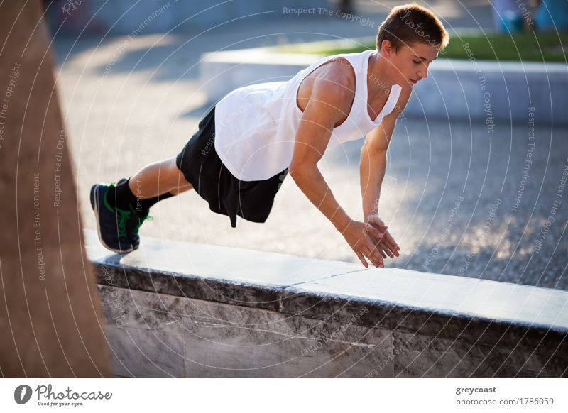 Teenager performing push-ups outdoor in city Lifestyle Body Sports Young man Youth (Young adults) Adults Hand 1 Human being 13 - 18 years Town Street Brunette