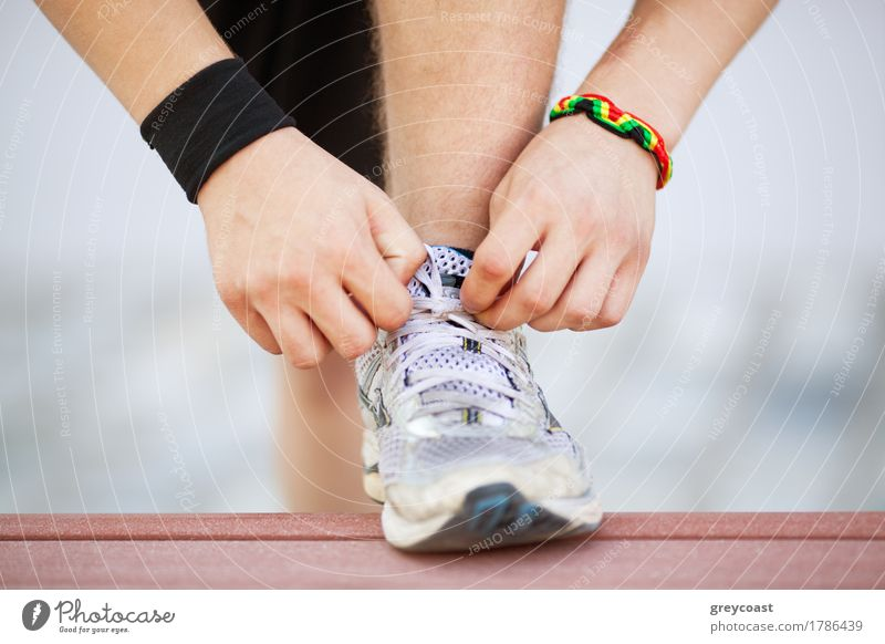 Close-up shot of man tying running shoes with foot on the bench. Getting ready before jogging. Going in for sports, healthy lifestyle Lifestyle Sports Jogging