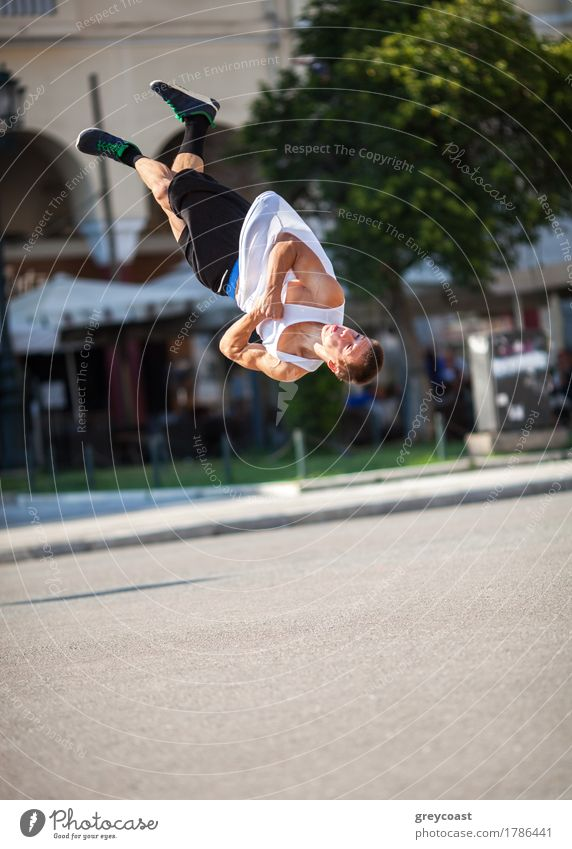 Young sportsman performing his acrobatic skills in doing somersault. Show in the city street Lifestyle Summer Sports Human being Man Adults Town Street Movement