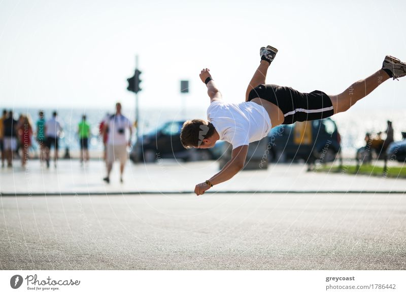 Young sportive man performing acrobatics in city square. Motion shot during tumbleset in the air Lifestyle Summer Sports Human being Man Adults Town Street