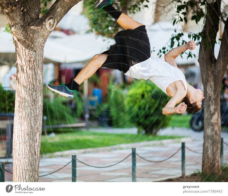 Motion shot of a young sportsman doing acrobatics in the city. Front flip trick Lifestyle Summer Sports Human being Man Adults Tree Town Street Movement Jump
