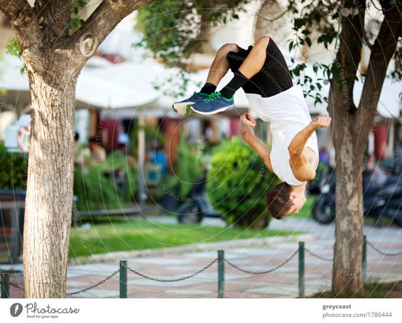 Young extreme athlete doing front flip between the trees. City street with outdoor cafe in background Lifestyle Freedom Summer Sports Human being Man Adults
