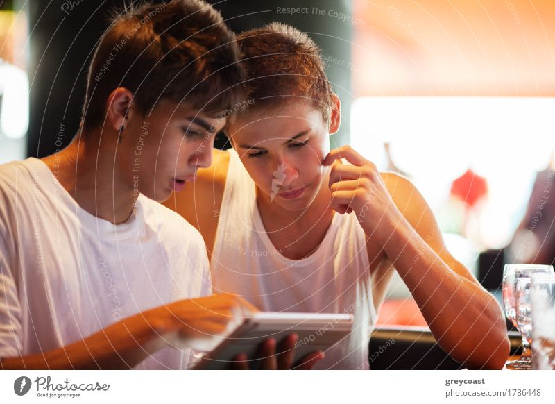 Two male teenagers surfing the internet on tablet computer while sitting in cafe. One young man pointing at screen Leisure and hobbies Entertainment Computer