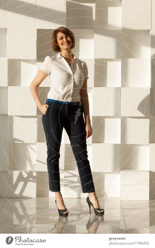 Smiling businesswoman in high heel shoes looking at camera while holding hand in pocket. Modern white wall on background Lifestyle Elegant Style Office Business