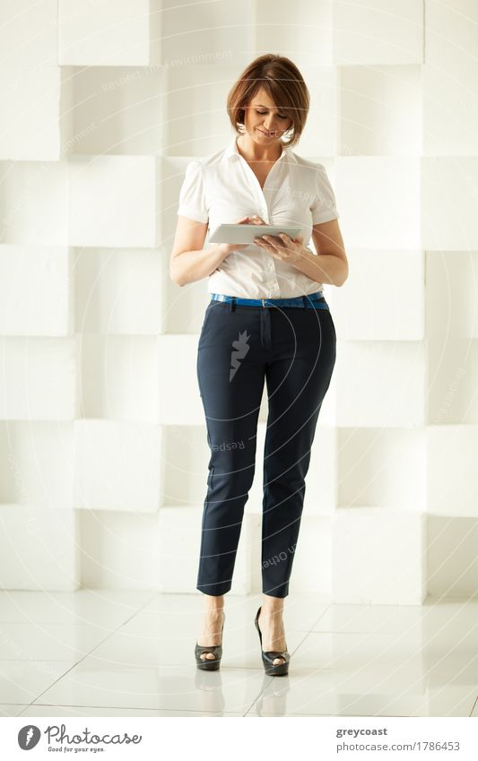 Smiling businesswoman standing against white wall while looking at tablet in her hand Lifestyle Elegant Style Office Business Adults Hand Elements Places Shirt