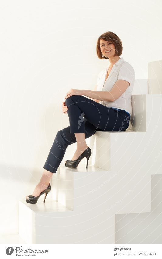 Elegant businesswoman looking at camera while sitting on stairs against of white wall Style Design Beautiful Calm Office Business Ladder Human being Woman