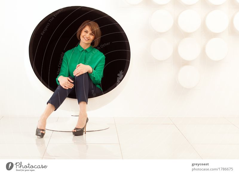 Attractive adult woman sitting on spherical chair with hands on knees. Modern white wall on background Lifestyle Elegant Style Chair Office Human being Woman