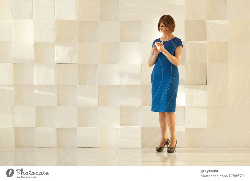 Woman in blue dress standing against modern wall while looking Lifestyle Elegant Style Office Telephone PDA Human being Adults Hand Places Clothing Dress