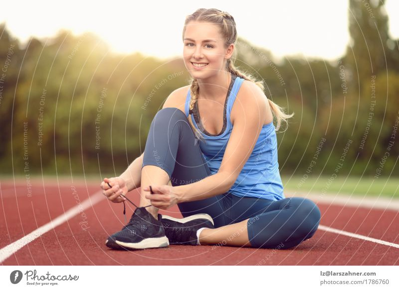Sporty young woman tieing her laces Human being Woman Youth (Young adults) Summer Beautiful Sun 18 - 30 years Adults Warmth Lifestyle Sports Copy Space Action