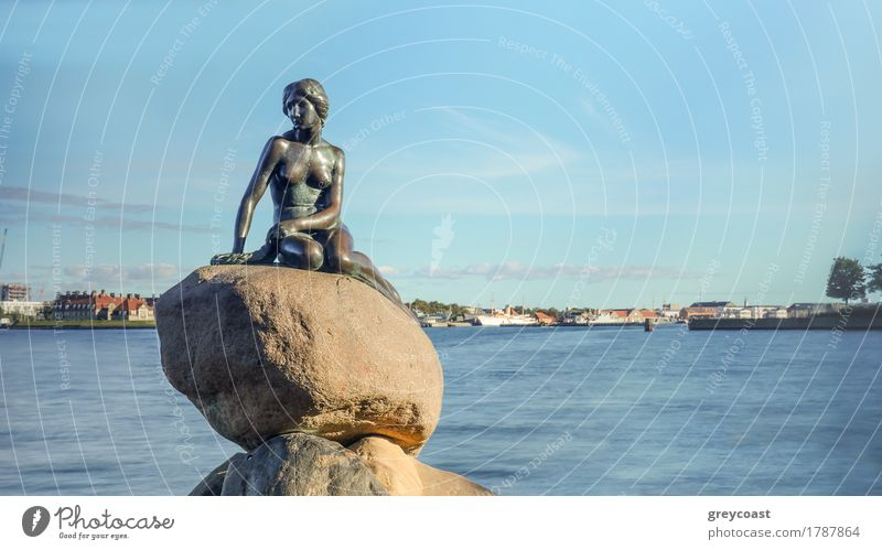 Front view of Little Mermaid statue on large boulders in Denmark with harbor under blue sky in the background Vacation & Travel Tourism Ocean Rock Harbour