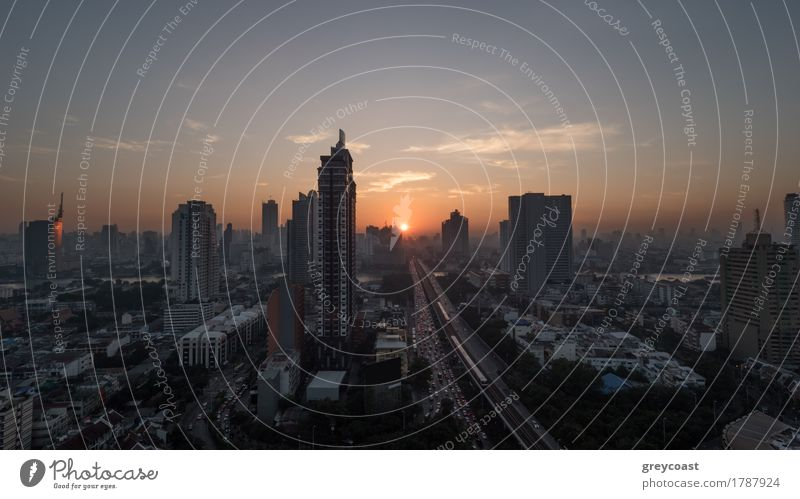 Sunset time in Bangkok, Thailand. City panorama with highrise urban architecture and traffic on highway. Sky in warm colors and sun going down Town High-rise