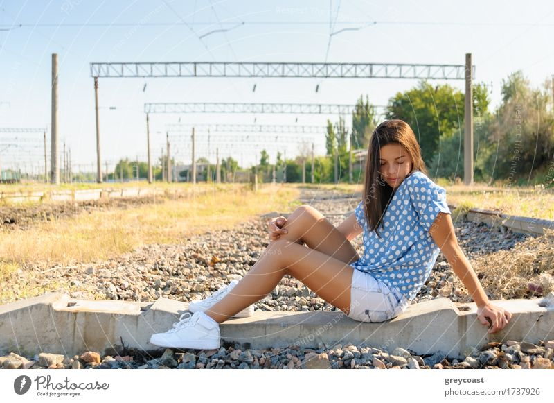 Teenager girl in city outskirts Human being Youth (Young adults) Summer Landscape Loneliness Girl 13 - 18 years Sit Concrete Railroad Trust Brunette Rural Town Horizontal Sneakers