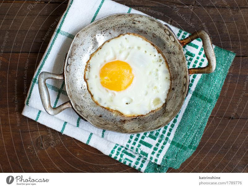 Fried egg in a old frying pan Herbs and spices Eating Breakfast Pan Table Fresh White Cholesterol Frying fried egg Meal Protein Rustic Unhealthy Close-up