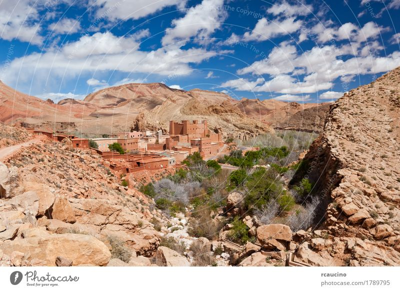 Ancient Kasbah in Dades Valley, south Morocco, Africa. Vacation & Travel Summer Mountain Landscape Sky Clouds Tree Oasis Village Stone Blue Yellow Green Red