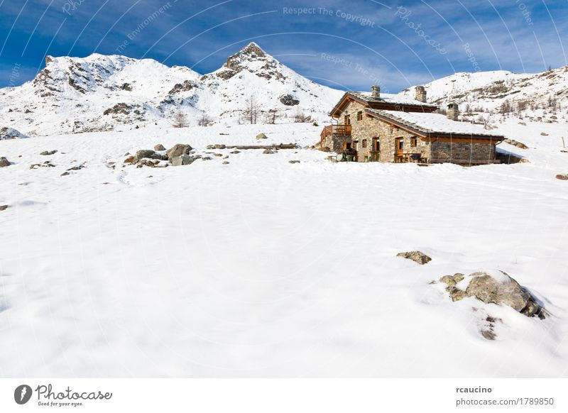 A mountain hut in a snowy mountain landscape. Val d'Aosta, Italy Vacation & Travel Tourism Adventure Winter Snow Mountain Nature Landscape Sky Clouds Rock Alps