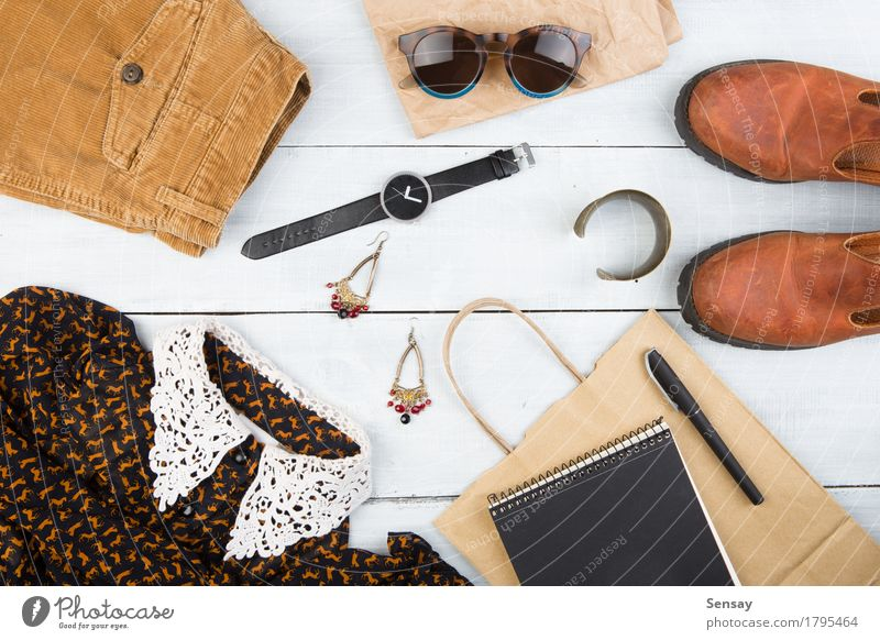 Womans stuff on the wooden table Shopping Style Design Vacation & Travel Tourism Table Clothing Dress Leather Accessory Sunglasses Footwear Boots Paper Pen Wood