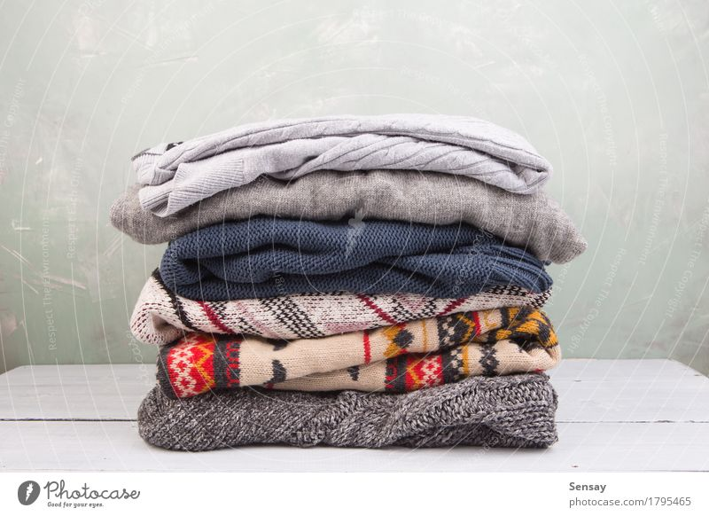 warm sweaters stacked on table White Winter Warmth Autumn Wood Fashion Clothing Soft Accumulation Cozy Stack Sweater Wool Comfortable Cupboard