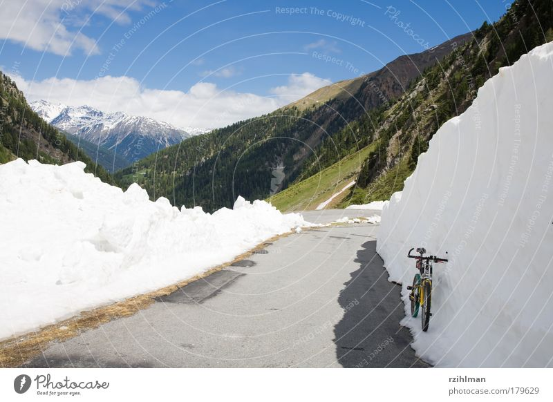 Snow wall at the Umbrail Pass Colour photo Exterior shot Copy Space left Day Sunlight Mountain Bicycle Clouds Hill Rock Alps Lanes & trails Driving Blue Gray