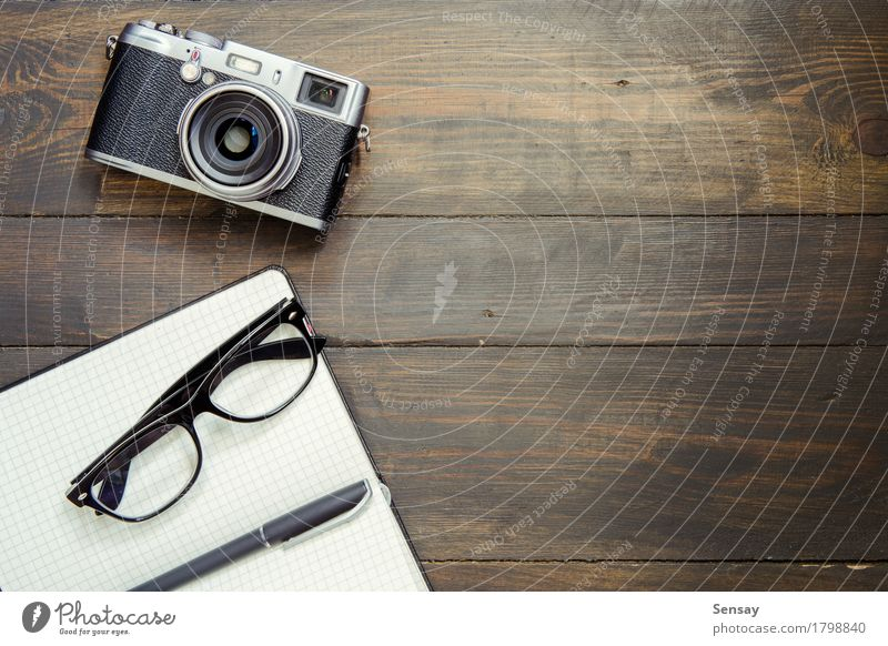 Camera, glasses and notepad on wood Old Style Wood Business Above Design Copy Space Office Retro Vantage point Table Paper Desk Pen Top