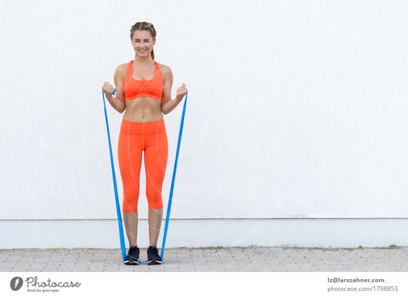 Young sporty woman doing exercises with a latex band Human being Woman Youth (Young adults) 18 - 30 years Adults Lifestyle Sports Happy Body Blonde Smiling Fitness Athletic Band Conceptual design Practice