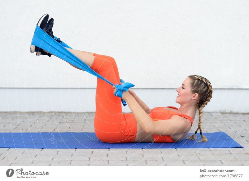 Young sporty woman doing exercises with a latex band Human being Woman Youth (Young adults) 18 - 30 years Adults Lifestyle Sports Feminine Happy Body Blonde
