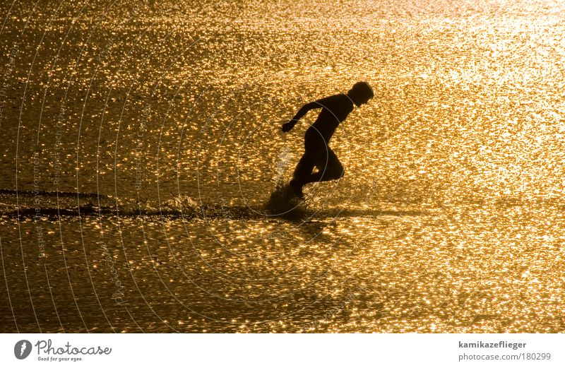 Human being Youth (Young adults) Water Ocean Beach Black Sports Freedom Adults Masculine Walking Drops of water Gold Running